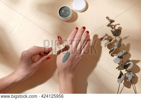 beauty, cosmetics and bodycare concept - hands with wooden spatula applying blue cosmetic clay mask to skin over branch of eucalyptus populus on beige background