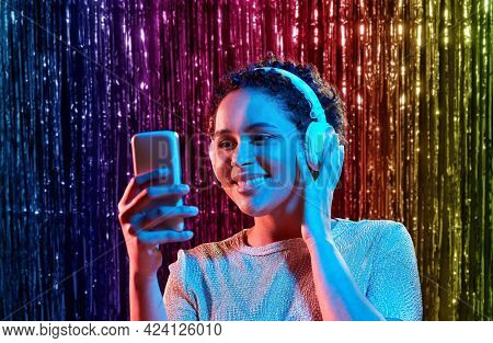 nightlife, fashion and people concept - happy young african american woman with smartphone and headphones at party in neon lights over rainbow foil curtain background