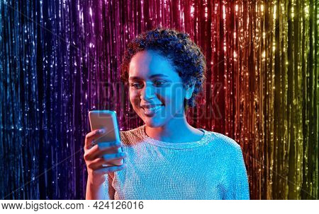 nightlife, technology and people concept - happy young african american woman with smartphone at party in neon lights over rainbow foil curtain background