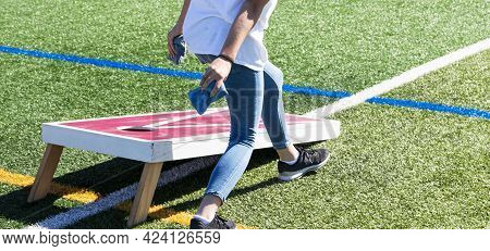 Rear View Of People Playing Cornhole With Homemade Wood Boards On A Green Turf Field.