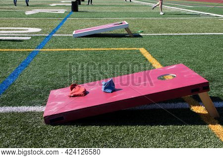 A High School Turf Field Is Set Up With Red And White Wooden Cornhole Games And Other Backyard Games