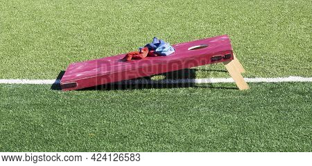 Side View Of A Homemade Solid Red Cornhole Game On A Green Turf Field With Blue And Red Bean Bags Re