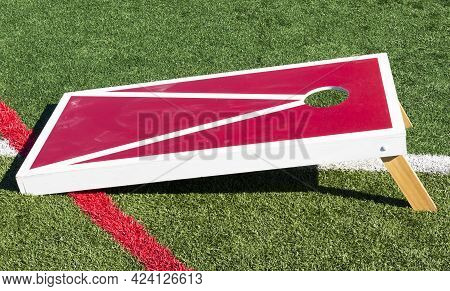 Side View Of An Homemadered And White Wood Cornhole Game Close Up On A Green Turf Field.