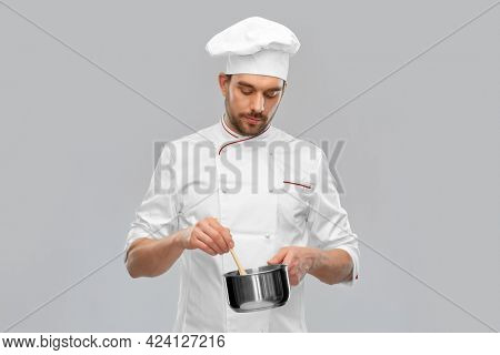 cooking, culinary and people concept - male chef in toque with pot or saucepan over grey background