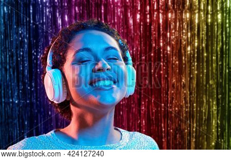 nightlife, technology and people concept - happy young african american woman in headphones listening to music at party in neon lights over rainbow foil curtain background