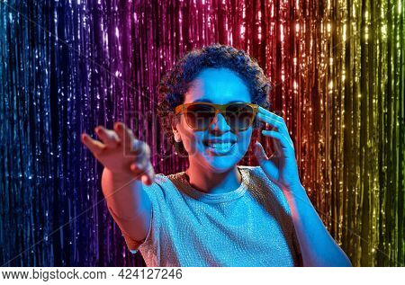 leisure, clubbing and nightlife concept - smiling young african american woman in sunglasses at party in ultraviolet neon lights over rainbow foil curtain background