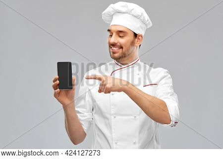 cooking, culinary and people concept - happy smiling male chef in toque showing smartphone over grey background