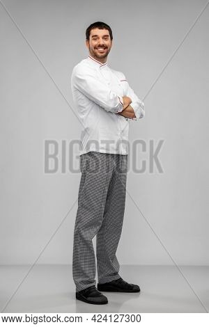 cooking, culinary and people concept - happy smiling male chef in jacket over grey background