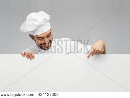 cooking, culinary and people concept - happy smiling male chef in toque with big white board over grey background