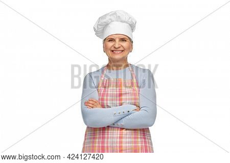 cooking, culinary and old people concept - portrait of smiling senior woman or chef in toque in kitchen apron with crossed arms over white background