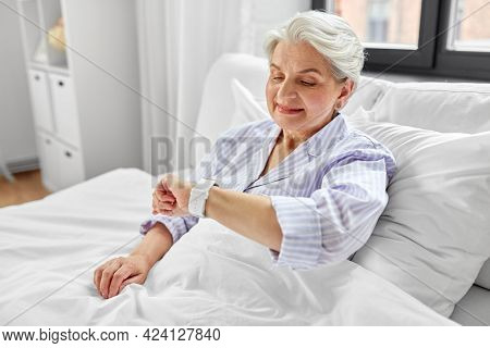 old age and people concept - happy smiling senior woman in pajamas with smart watch sitting in bed at home bedroom