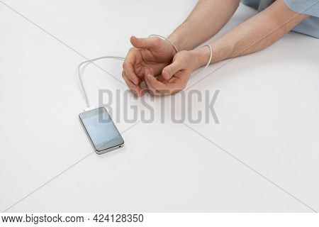 A Person Hands Addicted To The Digital Mobile Phone Device, Wire Tied To Arm