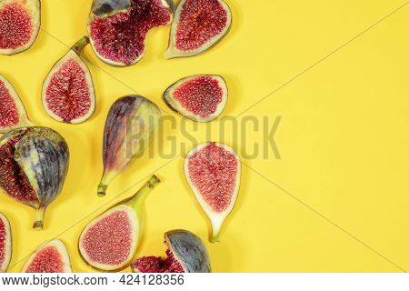 Whole Fruit And Slices Of Figs Are Spread Out On A Yellow Surface With Copyspace. Fig Fresh Fruits A