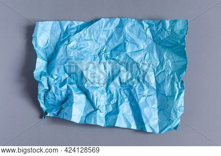 Crumpled Green Paper On A Blue Background. The Texture Of The Crumpled Paper For The Background.