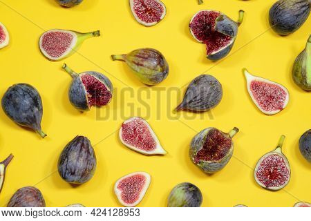 Whole Fruit And Slices Of Figs Are Spread Out On A Yellow Surface. Fig Fresh Fruits Are On The Yello