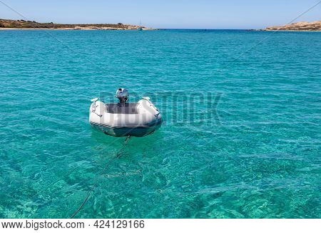 Dinghy Inflatable Boat On Turquoise Blue Sea Water