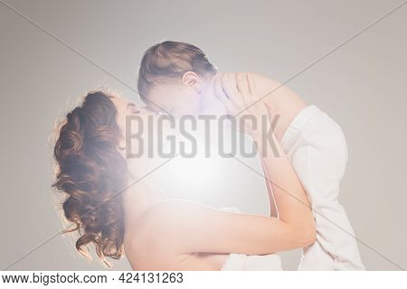Curly Mother With Bare Shoulders Kissing Baby Boy With Backlit On Grey Background.