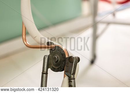Man Hands Bends Copper Pipes By Pipe Bender. Air Conditioner Technician Hands Bends Copper Pipes By