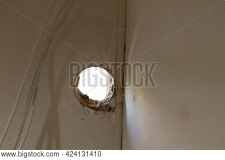 Holes On The Cement Wall Caused By Drilling. Hole In In White Cement Wall As A Background. Hole On T