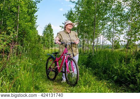 Grandma Rides A Bike. An Elderly Woman Rides A Bicycle In Nature.