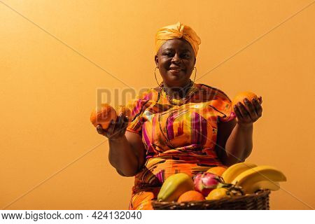 Smiling Middle Aged African American Saleswoman Sitting Near Fruits On Orange