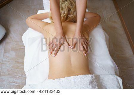 Professional Massage Therapist Massages The Back Of Adult Woman Lying On Massage Table, Close-up. La