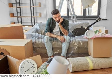 moving, eviction and real estate concept - sad man with boxes at new home