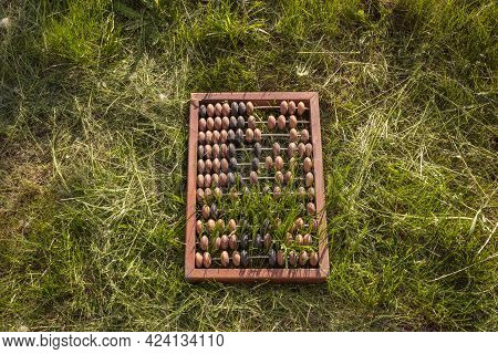 Old Abacus Is Located On Green Grass. View From Above. An Outdated Approach To Business.