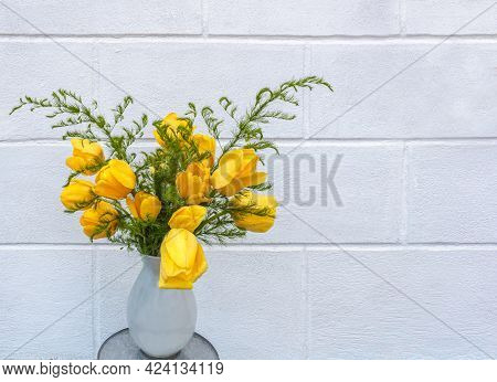 A Large Bouquet Of Bright Yellow Tulips With Green Leaves In A White Vase. The Background Is A White
