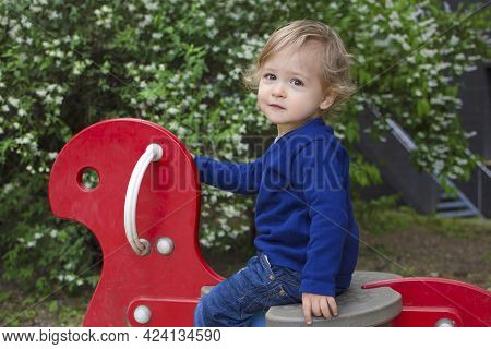 Cute Little Child Boy Having Fun Playing With Colorful Wooden Toys Outdoors In The Park, Beautiful S