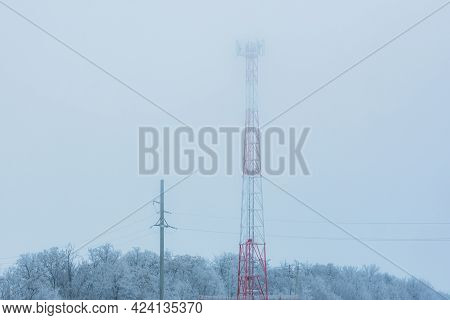 Cell Tower In The Winter Fog Close-up. Telecommunications Towers With Wireless Antennas In Rime. Ant