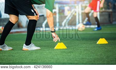 Coach Or Soccer Player Is Putting The Marker Cones For Soccer Training To Run And Jump.