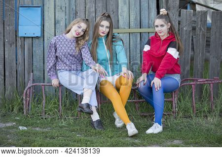 Girls In The Style Of The Nineties. Three Country Girls Are Sitting On A Wooden Bench.