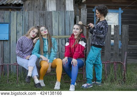Girls In The Style Of The Nineties. Country Girls Sit On A Wooden Bench By The Hut.