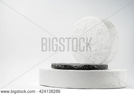 White And Black Round Pedestal Podium. Abstract Cement Pedestal By Spotlights On White Background