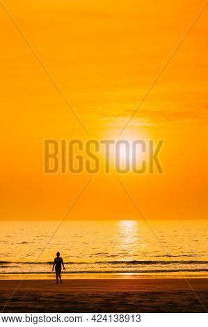 Dark Silhouette Of Young Caucasian Lady Woman In Swimsuit Walking In Sea Beach During Sunset. Vacati