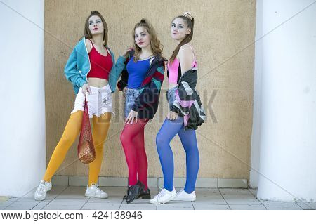 Three Beautiful Girls Dressed In The Style Of The Nineties Are Posing For The Camera.