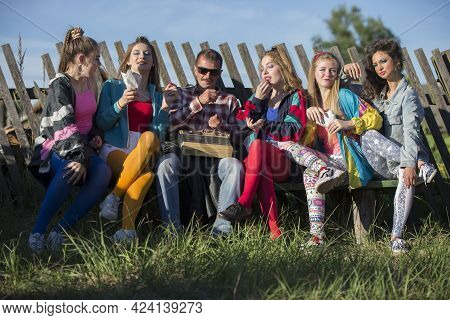A Group Of People Dressed In The Style Of The Nineties Sit On A Bench By A Skewed Fence.