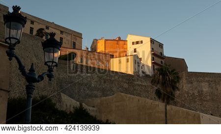 Coloring Of Facades During The Sunset In Calvi With The Old City Behind The Fortification On The Hil