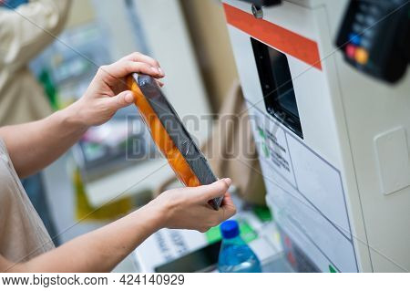 A Woman Scans Products At A Self-checkout Counter. Close-up Of Female Hands Self Buying Groceries In