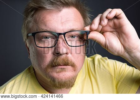 Portrait of an emotional man with glasses on a gray background adjusts glasses