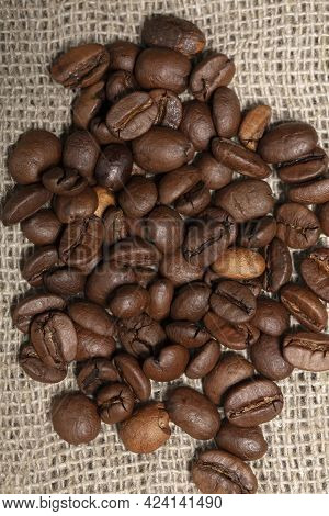 Coffee Beans Are Scattered Over The Burlap.