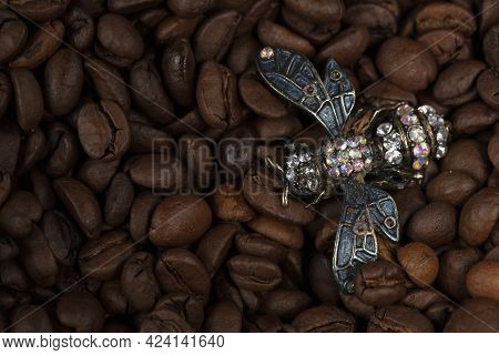 A Fly-shaped Brooch Lies On Scattered Coffee Beans.