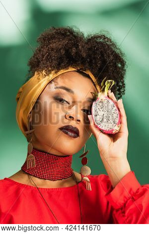 Young African American Woman In Headscarf Holding Half Cut Of Dragon Fruit On Green