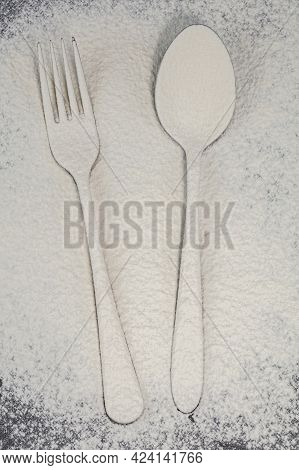 A Fork And Spoon On A Cutting Board Are Sprinkled With Flour.cutlery On The Board.