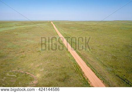 dirt remote road going through green prairie, Pawnee National Grassland in Colorado, aerial view