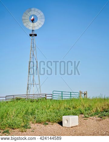 salt block for cattle and windmill pumping water in green prairie in Colorado - Pawnee National Grassland in early summer
