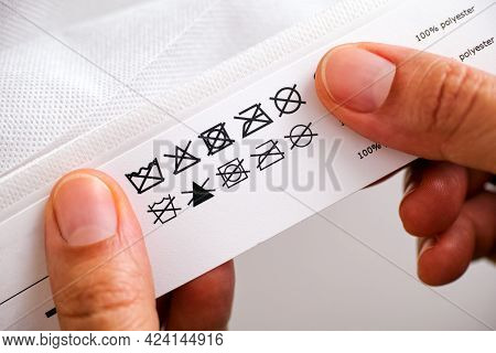 Woman's Hands Holding Label With Cleaning Instructions Of Polyester Thing - Do Not Wash; Do Not Blea