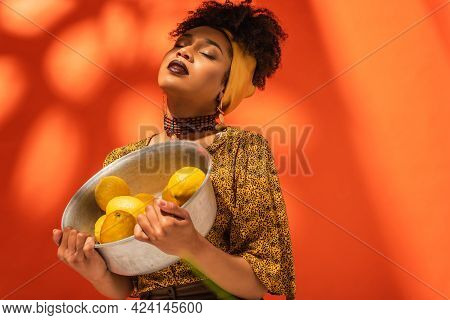 African American Woman In Blouse And Headscarf Holding Metal Bowl With Lemons On Orange