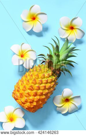 Yellow Pineapple And White Flowers On A Blue Background. Exotic Concept.